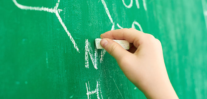 Close-up of children's hand with chalk on blackboard